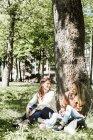 Women sitting against tree — Stock Photo