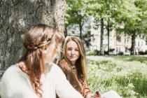 Female friends sitting on grassy field — Stock Photo
