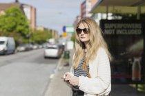 Woman wearing sunglasses holding phone — Stock Photo