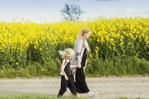 Irl walking with pregnant mother — Stock Photo