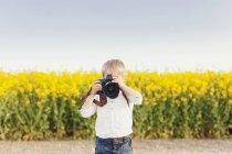 Мальчик фотографирует через камеру — стоковое фото