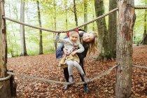 Feliz madre ayudar a chica equilibrio - foto de stock