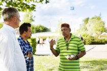 Male friends talking while playing boule — Stock Photo