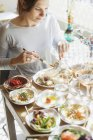 Woman eating food at table in restaurant — Stock Photo