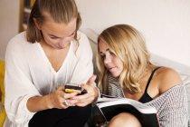 Young women using phone — Stock Photo