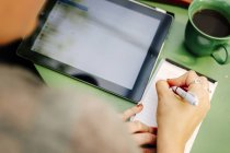 Woman writing on notepad — Stock Photo