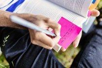 Scrittura dell'allievo sulla nota adesiva nel libro — Foto stock