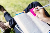 Student writing on adhesive note in book — Stock Photo