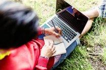 Hombre escribiendo notas y sosteniendo portátil - foto de stock