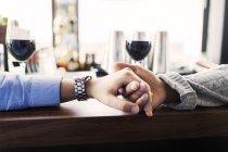 Gay men holding hands at bar counter — Stock Photo