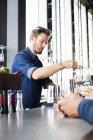 Barman en remuant le whisky dans le verre — Photo de stock