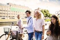 Jeunes amis avec des vélos marchant — Photo de stock