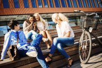 Happy young friends sitting outside — Stock Photo