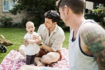 Gay couple playing with baby girl — Stock Photo