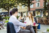 Friends sitting at sidewalk cafe — Stock Photo