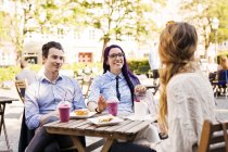 Friends talking at sidewalk cafe — Stock Photo