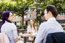 Friends talking at sidewalk cafe — Stock Photo