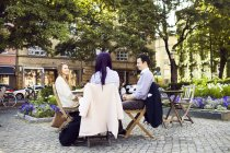 Women and man sitting at cafe — Stock Photo