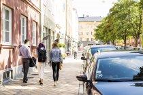 Amici che camminano sul marciapiede — Foto stock
