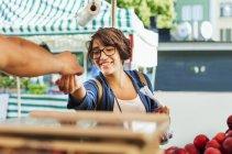 Smiling girl buying fruits — Stock Photo