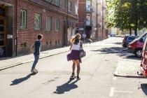 Vista posteriore di ragazze skateboard sulla strada — Foto stock