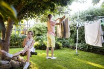 Girl on swing and brother doing laundry — Stock Photo