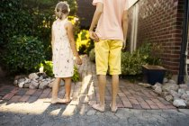 Brother and sister standing in garden — Stock Photo