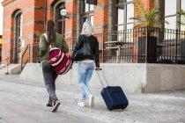 Female students with luggage walking — Stock Photo
