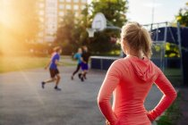 Спортивная женщина смотрит на друзей, играющих — стоковое фото
