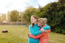 Счастливые женщины обнимаются на поле — стоковое фото