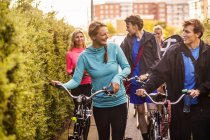 Friends walking with bicycles — Stock Photo