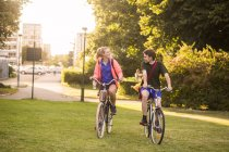 Girl and boy riding bicycles — Stock Photo