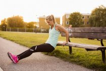 Ragazza che fa esercizio su panchina — Foto stock