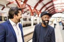 Empresarios contentos en la estación de ferrocarril - foto de stock