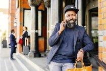Homme souriant utilisant un téléphone intelligent — Photo de stock