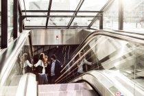 Gente di affari sulla scala mobile — Foto stock