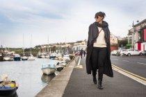 Женщина, идущая по гавани — стоковое фото