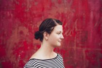 Woman standing against red wall — Stock Photo