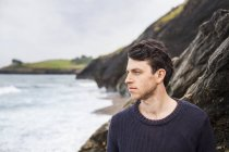 Jeune homme regardant loin de la plage — Photo de stock
