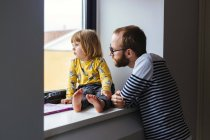 Man with daughter looking through window — Stock Photo