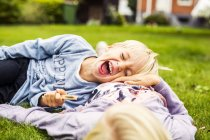 Cheerful boy lying on his sisters stomach — Stock Photo