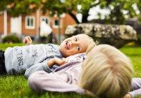 Мальчик, лежащий на животе сестер — стоковое фото