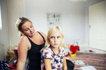 Mère faisant cheveux filles à la maison — Photo de stock