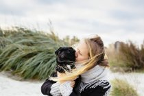 Young woman kissing dog — Stock Photo