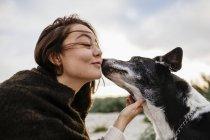 Cão beijando jovem mulher — Fotografia de Stock