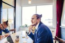 Giovani uomo d'affari premuroso che si siede al tavolo — Foto stock