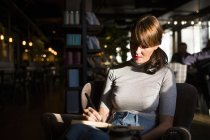 Женщина сидит в кафе — стоковое фото