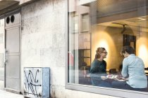 Businessman and businesswoman seen through glass — Stock Photo