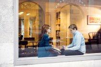 Businessman and businesswoman seen through window — Stock Photo