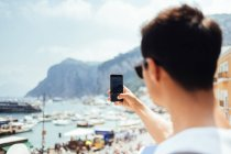 Young man photographing with smartphone — Stock Photo